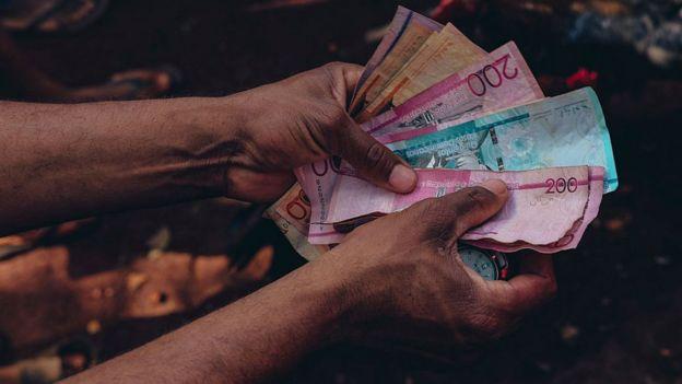 Hombre sostiene billetes.
