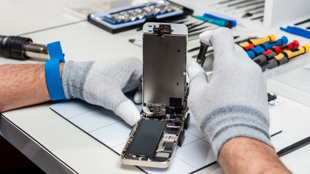 Two hands repairing a cell phone in a workshop.