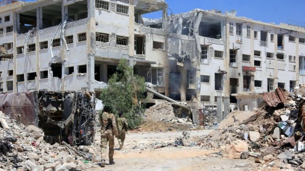 Forces loyal to President Bashar al-Assad walk past ruined buildings in the Castello road in Aleppo, Syria