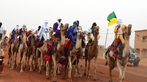 Dignitaries in traditional attire ride camels to the stadium in Gao on July 18, 2018 as the incumbent Malian President Ibrahim Boubacar Keita is expected to address a campaign rally.