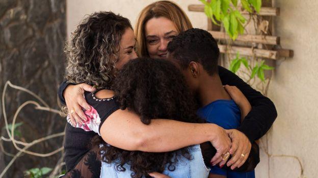 Os irmãos Jessica e Lucas com as mães que os adotaram, Sandra e Elísia
