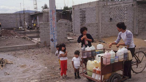 Vendedor ambulante de sucos cercado por crianças