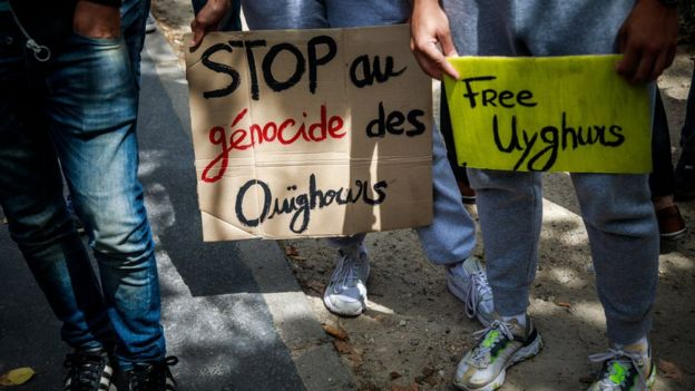 """Demonstrators hold posters reading """"Stop Uyghurs Genocide and Free Uyghurs"""" during a gathering against China""""s alleged abuse of the Muslim Uyghurr community in Xinjiang province, near the Chinese embassy in Paris, France, 25 July 2020."""