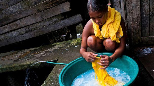 Una mujer lava ropa frente a una casa de madera.