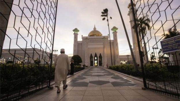 Warga berjalan di depan Masjid Sultan Omar Ali Saifuddien di Bandar Seri Begawan, Brunei, 1 April 2019, untuk salat magrib.