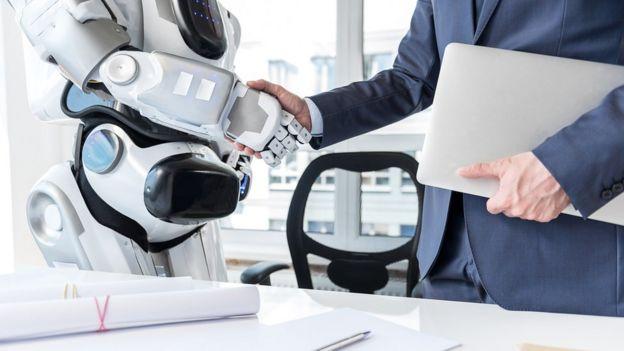 Hombre y robot dándose la mano