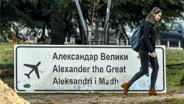 A woman walks past the removed sign for the airport Alexander the Great in Skopje on February 19, 2018