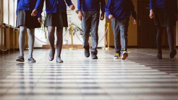 Pernas de cinco estudantes caminhando em corredor, entre meninos e meninas