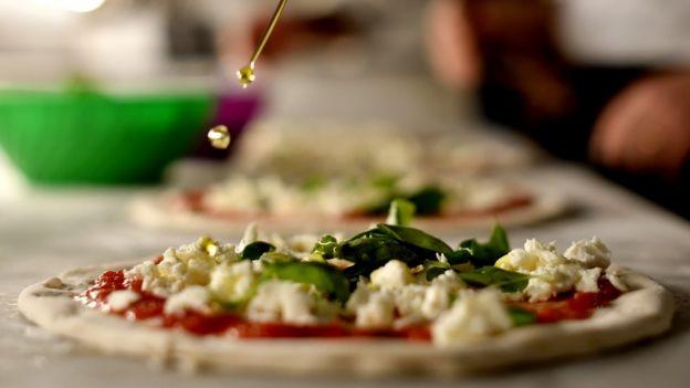 Imagem mostra pizza sendo preparada