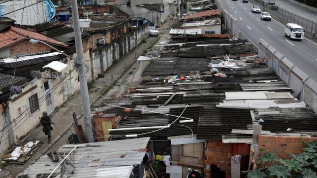 Militar caminha em favela ao lado de avenida
