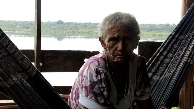 Idosa indígena sentada em uma rede ao lado de um rio em região próxima à estrada