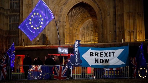 Anti-Brexit protesters with signs and EU flags lit up with fairy lights stand next to pro-Brexit banners outside the Houses of Parliament in London on September 9, 2019 as MPs debate