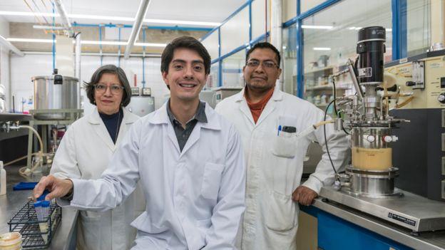 Javier sorri ao lado de dois membros de sua equipe, todos de jaleco dentro de um laboratório