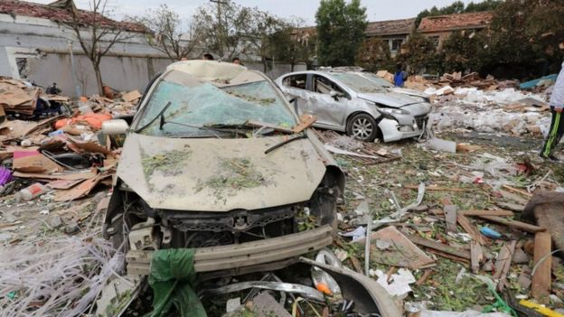 Two cars are pictured totally destroyed surrounded by debris