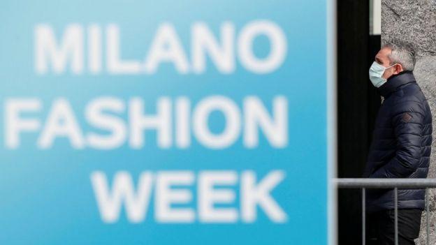 человек в маске на фоне стенда Миланской недели моды