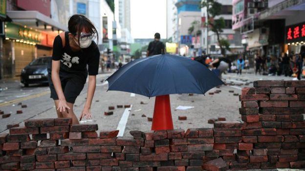 Una manifestante construye un muro