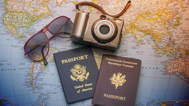 Dos pasaportes, unas gafas y una cámara sobre un mapa mundi.