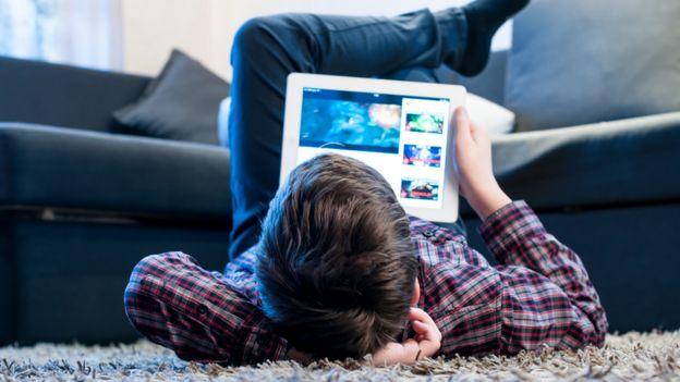 Niño acostado en el suelo con una tableta