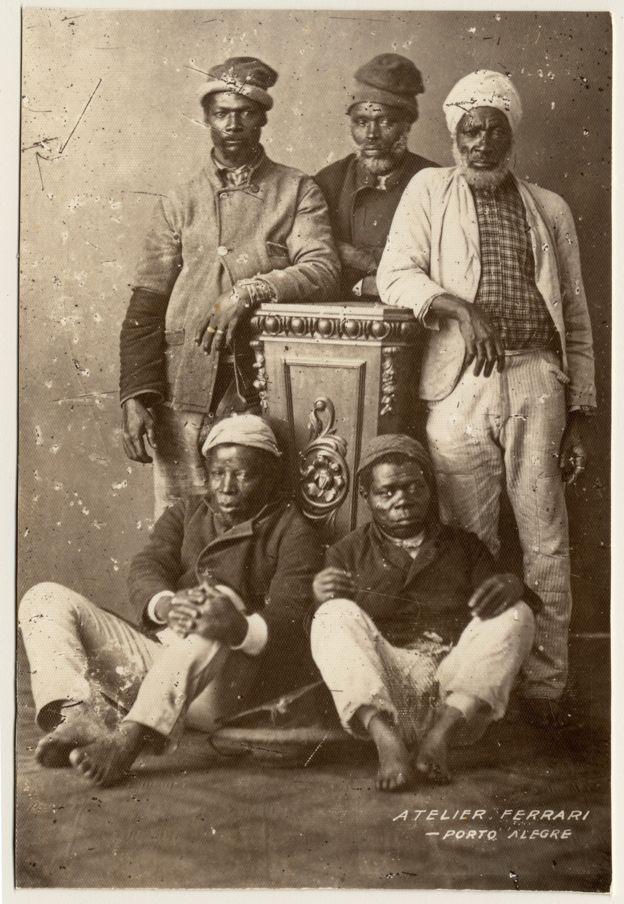 Imagem mostra três homens negros de pé e dois sentados. São ex-escravos fotografados em um estúdio de Porto Alegre no final do século XIX. Crédito: Acervo do Museu de Porto Alegre Joaquim Felizardo/Irmãos Ferrari