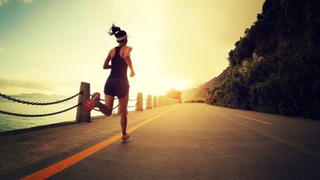 Una chica corriendo al lado del mar y de la montaña.