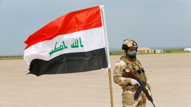 جندي يرتدي كمامة وقفازات يقف متقلدا سلاحه إلى جانب العلم العراقي