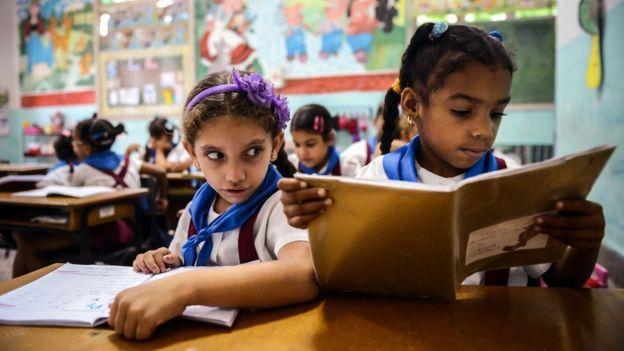 Niñas cubanas leen en clase.