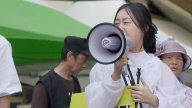 Woman shouts through a megaphone at Incheon Queer Festival