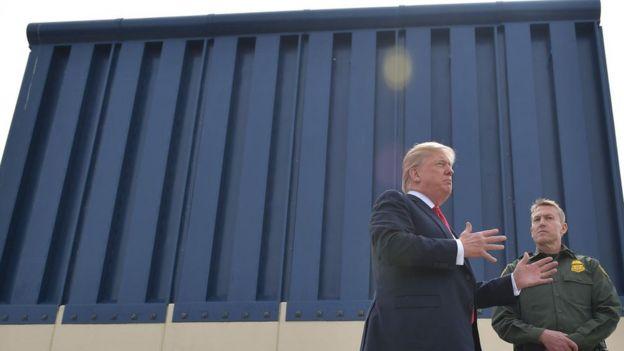 Donald Trump junto a un trozo de muro fronterizo.