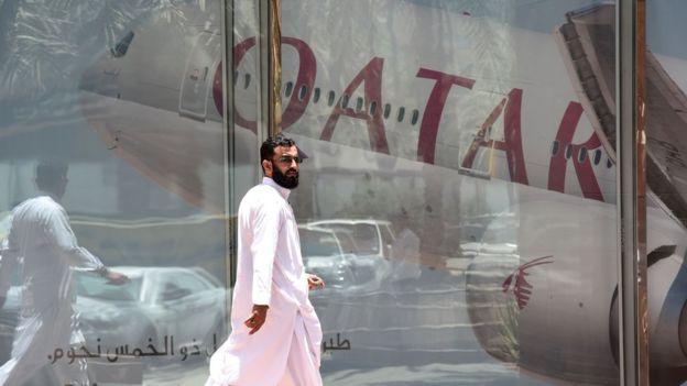 Homem em frente de aeronave da Catar Airways