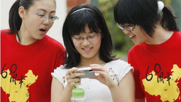 Chinese students attending the Nanyang Girls' High School look at a digital camera