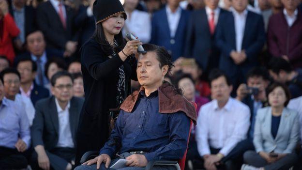 Hwang Kyo-ahn afitándose la cabeza