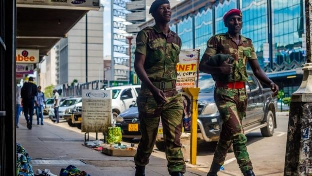 Zimbabwean soldiers walk by main streets in the Central Business District of Harare on November 20, 2017.