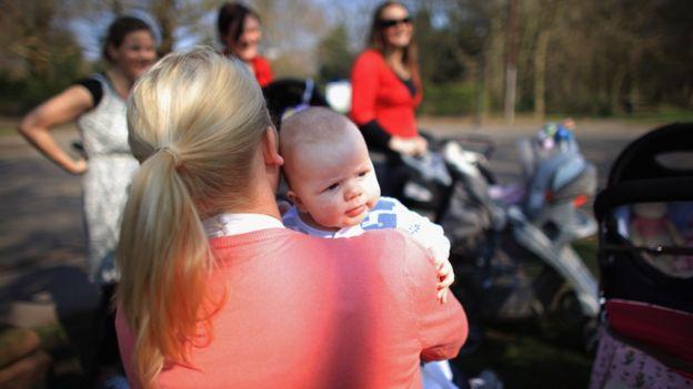 Madre con bebé al hombro.