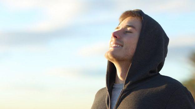 Hombre joven tomando una respiración profunda.