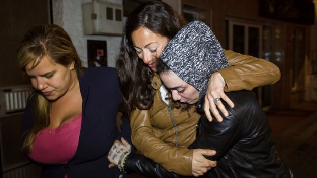 Ms Rico's sister Maria del Valle (C) holds on to her after she arrived back in Spain