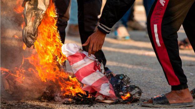 Manifestante queimando bandeira dos Estados Unidos