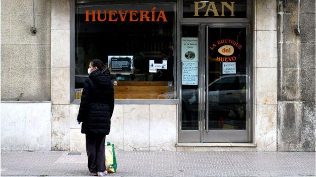 Женщина у закрытой лавки хлеба и яиц в испанском Бургосе 31 марта 2020 года