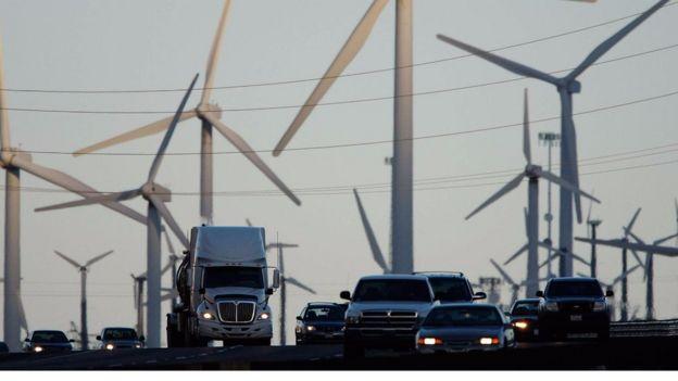 Camiones y vehículos entre molinos de energía eólica.