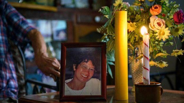 Una fotografía de la esposa de Aclo, rodeada de velas y flores