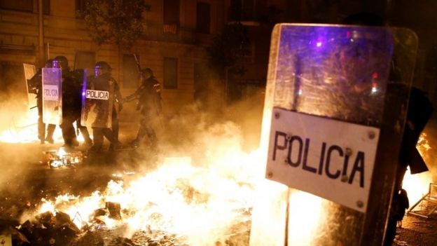 Police officers stand guard amid burning barricades in Barcelona. Photo: 16 October 2019