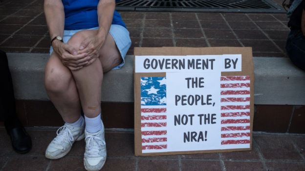"""A woman sits by a sign that says """"Government for the people not the NRA"""""""