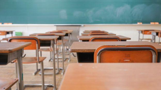 Carteiras em uma sala de aula, com lousa ao fundo