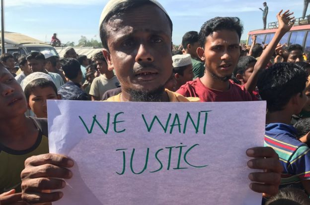 Rohingya protester in Cox's Bazar holds up placard demanding justice