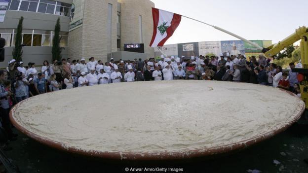 gente conglomerada ante un gigantesco plato de humus.