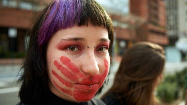 Chica joven con una mano roja pintada en la cara
