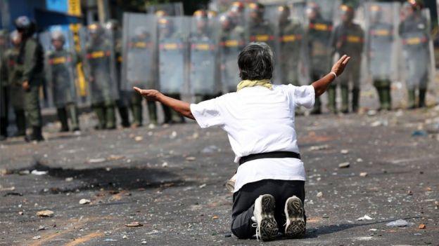 A demonstrator kneels down in front of security forces in Urena, Venezuela