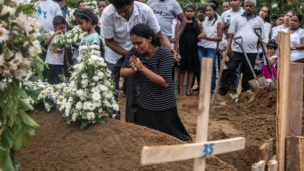 """A woman grieves at the grave after a funeral for a person killed in the Easter Sunday attack on St Sebastian""""s Church, on April 25, 2019"""