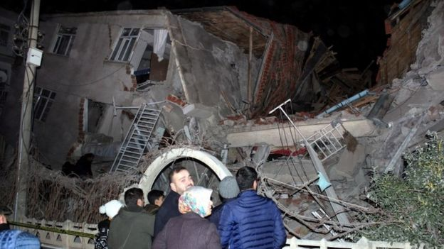 People stand outside collapsed building - 24 January