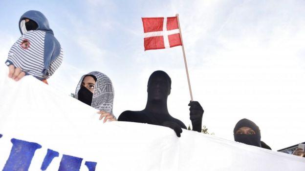 Imagem mostra pessoas com o rosto coberto e um boneco empunhando a bandeira da Dinamarca, em protesto realizado na cidade de Copenhague, no primeiro dia da implementação da proibição do véu no país
