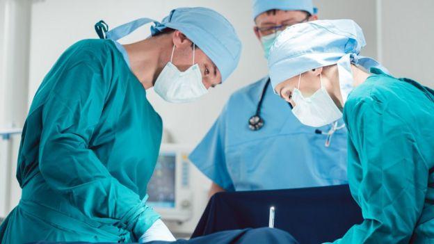 Doctores practicando una cesárea
